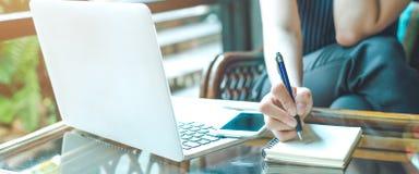 Handen för affärskvinnan skriver på en notepad med en penna och använder en bärbar datordator royaltyfria foton