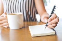 Handen för affärskvinnan skriver på notebookwith en penna Arkivbild