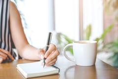 Handen för affärskvinnan skriver på notepaden med en penna i offien Royaltyfri Fotografi