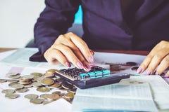 handen för affärskvinnan som beräknar hennes månatliga kostnader under skatt, kryddar med mynt, räknemaskin, royaltyfria bilder