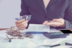 Handen för affärskvinnan som beräknar hennes månatliga kostnader under skattsäsong med mynt, räknemaskinen, kreditkorten och kont royaltyfria bilder