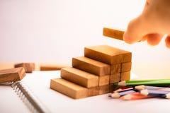 Handen för affärsmannen satte träkvarter i formen av en trappuppgång arkivbilder