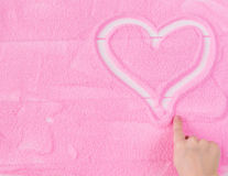 Handen för barn` s drar en hjärta på den dekorativa sanden arkivfoto