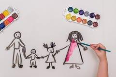 Handen för barn` s målar en lycklig familj Arkivfoto