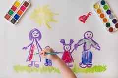 Handen för barn` s målar en lycklig familj Arkivbild