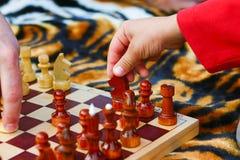 Handen för barn` s tar ett schackstycke Royaltyfri Bild
