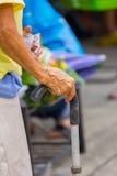 Handen för den gamla kvinnan lutar på att gå pinnen, närbild Arkivbild