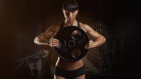 Handen för den muskulösa kvinnan för kondition som tränga sig in den starka pumpar upp, med plattan royaltyfri fotografi