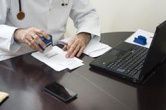 Handen för doktors` s stämplade på receptet Doktorn skriver ett recept på hans skrivbord Arkivbild