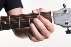Handen för gitarrist` s klämmer fast ackordet A på gitarren, på en vit bakgrund Horisontal inrama royaltyfri bild