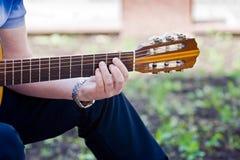 Handen för gitarrist` s rymmer gitarren royaltyfri bild