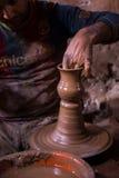 Handen för keramiker` s formar leran som pitcherlying på hjulet för snurrkeramiker` s Arkivbild