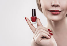 Handen för kvinna` s med en flaska av rött spikar polermedel bakgrund isolerad white Royaltyfri Bild
