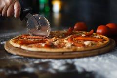 Handen för kvinna` s med en kniv klippte pizza på svart bakgrundsnärbild arkivfoton