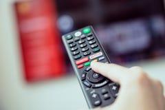 Handen för kvinna` s rymmer en TVfjärrkontroll med tryckning av massmediaservice arkivbild