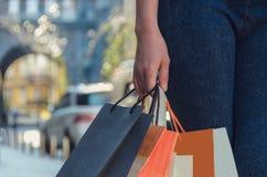 Handen för kvinna` s rymmer mycket pappers- mångfärgade påsar shopping royaltyfria bilder