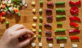 Handen för kvinna` s samlar även rad av färgrika fryste blandade grönsaker på en träbakgrund royaltyfria bilder