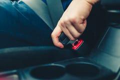 Handen för man` s fäster säkerhetsbältet av bilen Stäng ditt bilsäte arkivfoto