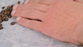 Handen för man` s krattar kaffebönor på konkret yttersida stock video