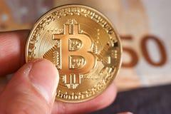 Handen för man` s med bitcoin och 50 femtio euro av bakgrunder fakturerar sedelmakro Arkivfoton