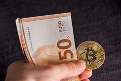 Handen för man` s med bitcoin och 50 femtio euro av bakgrunder fakturerar sedlar Royaltyfri Fotografi