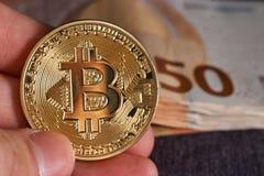 Handen för man` s med bitcoin och 50 femtio euro av bakgrunder fakturerar sedlar Makro Arkivbild