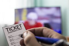 Handen för man` s rymmer en biljett för bookmaker` s, och pennan, på TV:N går hockey, sportar som slå vad, slut-UPS royaltyfri foto
