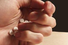 Handen för man` s rymmer en hög av vita preventivpillerar arkivbild