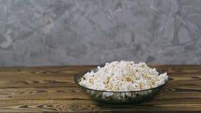 Handen för man` s sätter exponeringsglas med kolsyrat vatten nära den glass bunken mycket av popcorn stock video