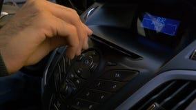 Handen för man` s sätter skivan in i bilspelaren Knappkontroll för CD-spelare i en bil Handen sätter skivan in i Fotografering för Bildbyråer