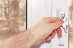 Handen för person` s stänger fönstret på låsnärbilden arkivbild