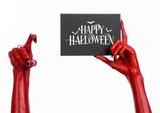 Handen för röd jäkel med svart spikar att rymma ett pappers- kort med den lyckliga allhelgonaaftonen för ord Arkivfoto