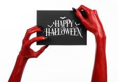 Handen för röd jäkel med svart spikar att rymma ett pappers- kort med den lyckliga allhelgonaaftonen för ord Arkivfoton