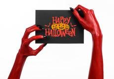 Handen för röd jäkel med svart spikar att rymma ett pappers- kort med den lyckliga allhelgonaaftonen för ord Royaltyfri Fotografi
