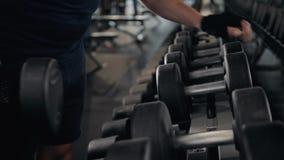 Handen för ` s för den starka mannen tar en tung hantel i idrottshallen, slut upp grabb för inomhus sport för makro lager videofilmer