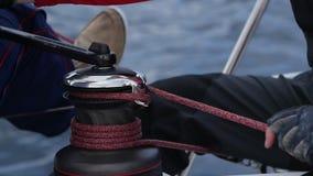 Handen för sjöman` s drar repet på vinschen av yachten