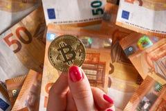 Handen för Woomen ` s med bitcoin och 50 femtio euro av bakgrunder fakturerar sedlar Fotografering för Bildbyråer