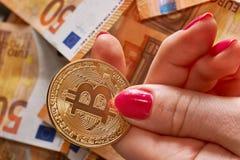 Handen för Woomen ` s med bitcoin och 50 femtio euro av bakgrunder fakturerar sedlar Royaltyfri Bild