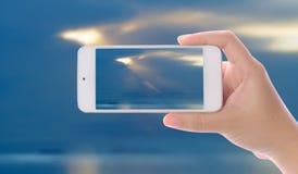Handen fotograferade härlig havssoluppgång, genom att använda smartphonen Royaltyfri Fotografi