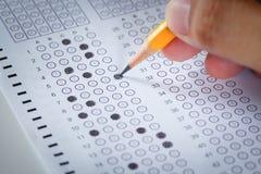 Handen fyller in arket och blyertspennan för examenkarbonpapperdator Arkivfoton