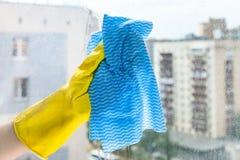 Handen gör ren exponeringsglas av det hem- fönstret i stads- hus fotografering för bildbyråer