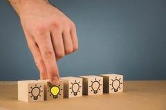 handen g?r ett val och v?ljer en brinnande ljus kula, ett symbol av en ny id? royaltyfri fotografi