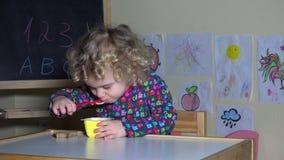 Handen ger gullig liten flickayoghurt och panerar och litet barnbarnstart för att äta arkivfilmer