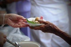 Handen ger mat till händer av en tiggare Arkivbild