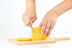 Handen gesneden kaas op een houten scherpe raad Royalty-vrije Stock Afbeeldingen
