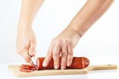 Handen gesneden salami op een scherpe raad Royalty-vrije Stock Afbeelding