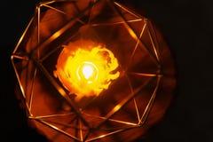 Handen - gjorde bivaxstearinljuset i en candleholder på träskiva arkivbilder