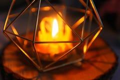 Handen - gjorde bivaxstearinljuset i en candleholder på träskiva arkivfoton