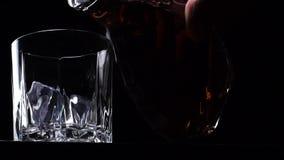 Handen häller whisky, eller alkoholdrinken på burk i ett fasetterat exponeringsglas arkivfilmer