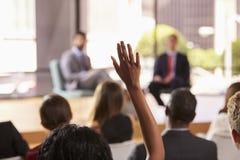Handen i åhörare lyftte för en fråga på ett affärsseminarium arkivfoto